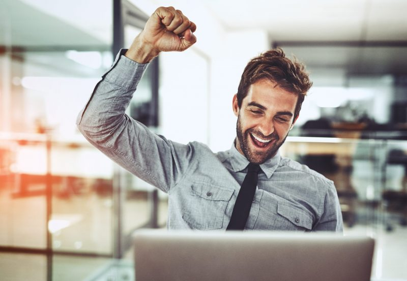 Shot of a handsome young businessman doing a fist pump while working on a laptop in an office